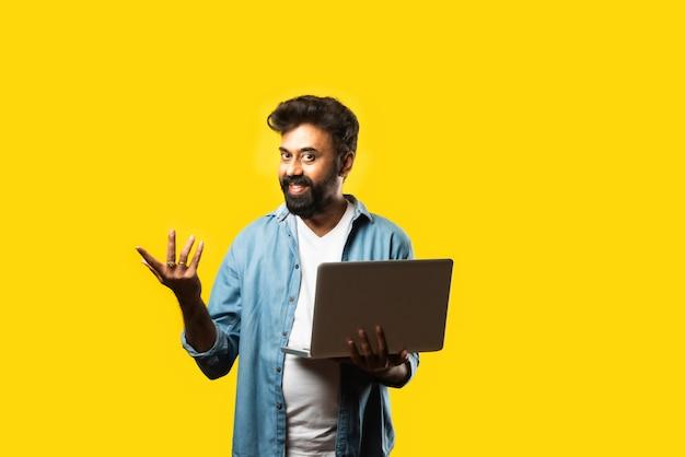 Jeune homme barbu asiatique indien dans des vêtements décontractés à l'aide d'un ordinateur portable en se tenant debout sur du jaune