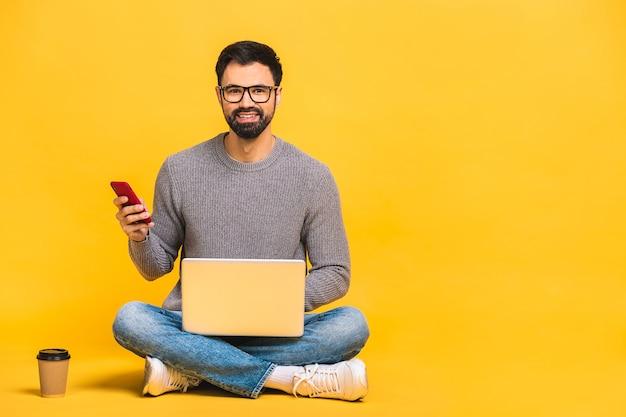 Jeune homme barbu assis sur le sol avec un ordinateur portable et parler au téléphone. isolé sur fond jaune.