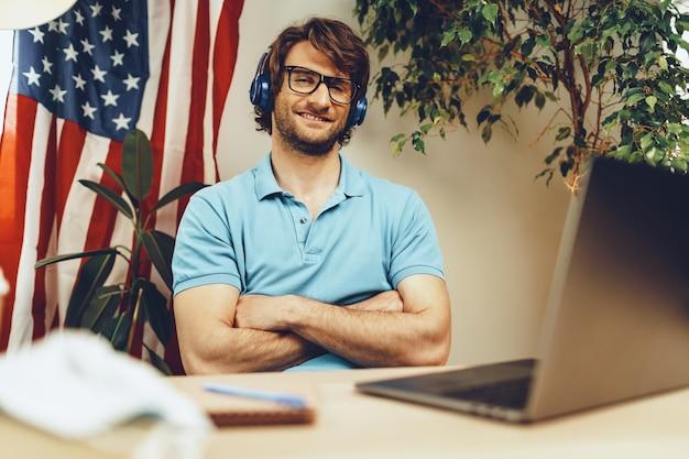 Jeune homme barbu assis à table avec ordinateur portable et drapeau américain, homme patriote