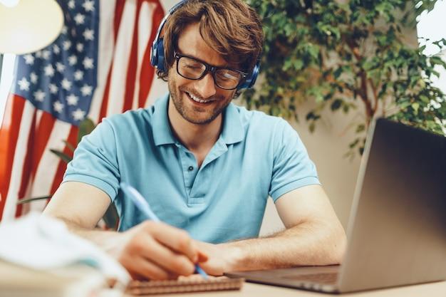 Jeune homme barbu assis à table avec ordinateur portable et drapeau américain