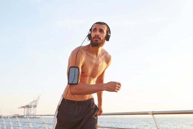 Jeune homme barbu athlétique fonctionnant au bord de la mer, regardant ailleurs et écoutant des chansons préférées sur des écouteurs,