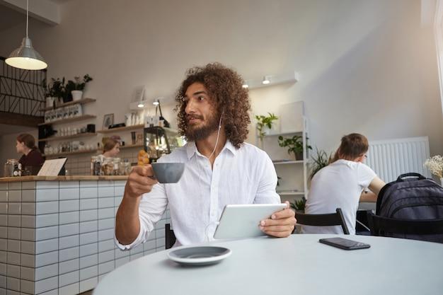 Jeune homme barbu attrayant assis à table dans un café avec une tasse de café et de tablette, regardant de côté avec étonnement, portant une chemise blanche et des écouteurs