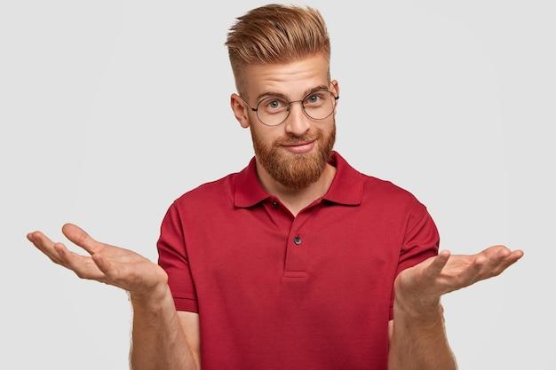 Un jeune homme barbu attrayant et douteux avec des cheveux roux, une barbe épaisse et une moustache, hausse les épaules, doute de ce qu'il faut acheter, a un look attrayant, pose contre un mur blanc. concept d'hésitation