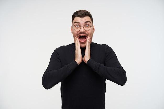 Un jeune homme barbu aux cheveux noirs assez perplexe tenant des paumes sur son visage tout en regardant avec étonnement avec de grands yeux et la bouche ouverte, isolé sur blanc