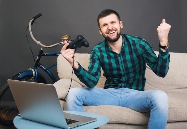 Jeune homme barbu beau hipster assis sur un canapé à la maison, jouant au jeu vidéo sur ordinateur portable