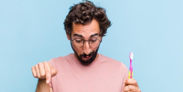 Jeune homme barbu avec la bouche ouverte pointant vers le bas avec les deux mains, l'air choqué, étonné et surpris