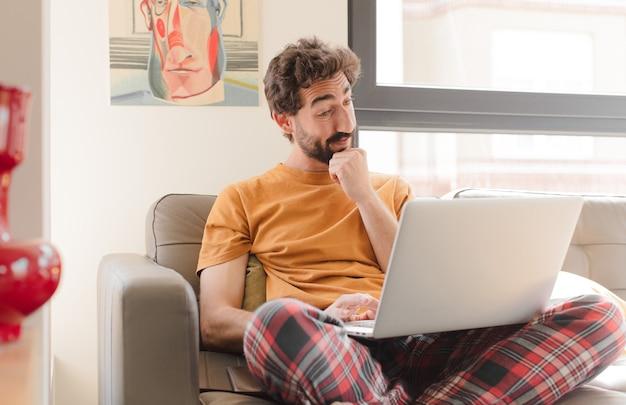 Jeune homme barbu sur un canapé avec un ordinateur portable