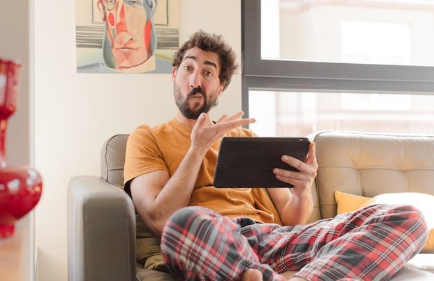 Jeune homme barbu sur un canapé avec une tablette à écran tactile