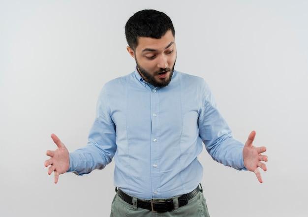 Jeune homme barbu en chemise bleue montrant un geste de grande taille avec les mains surpris debout sur un mur blanc