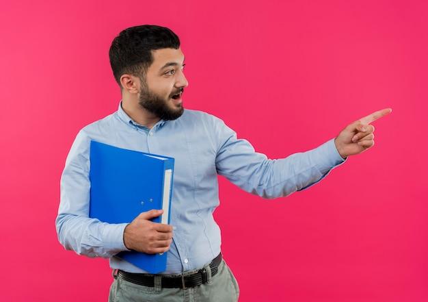 Jeune homme barbu en chemise bleue tenant le dossier pointant avec l'index à quelque chose de souriant