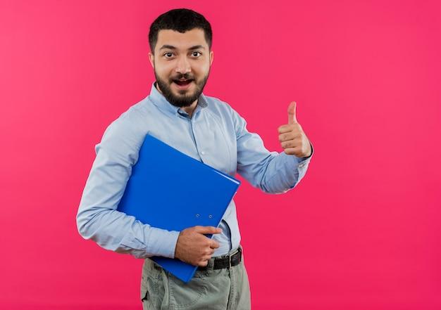 Jeune homme barbu en chemise bleue tenant le dossier souriant montrant les pouces vers le haut