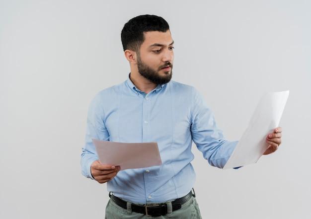 Jeune homme barbu en chemise bleue tenant des pages blanches en les regardant avec un visage sérieux debout sur un mur blanc
