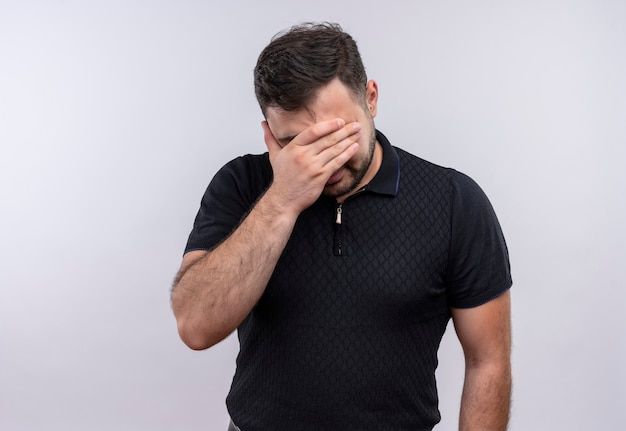Jeune homme barbu en chemise noire à la fatigue et l'ennui couvrant les yeux avec bras