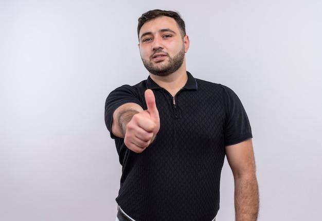 Jeune homme barbu en chemise noire heureux et positif montrant les pouces vers le haut
