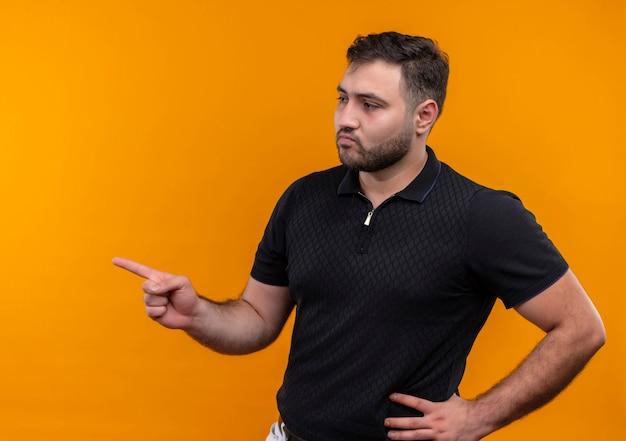 Jeune homme barbu en chemise noire pointant avec l'index sur le côté à côté avec une expression confiante sérieuse