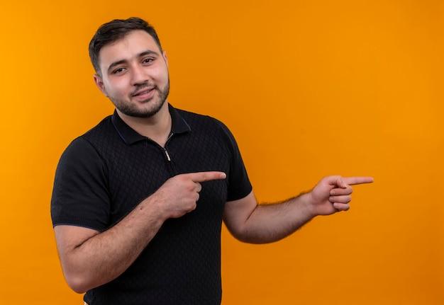 Jeune homme barbu en chemise noire pointant avec l'index sur le côté regardant la caméra avec une expression confiante