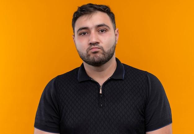 Jeune homme barbu en chemise noire regardant la caméra mécontent