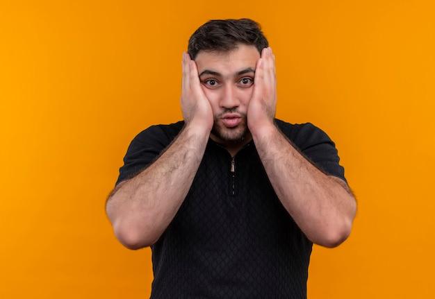 Jeune homme barbu en chemise noire regardant la caméra surpris et étonné touchant le visage avec les bras