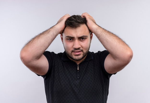 Jeune homme barbu en chemise noire a souligné et nerveux tirant ses cheveux