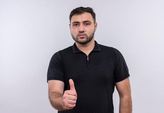 Jeune homme barbu en chemise noire souriant heureux et positif montrant les pouces vers le haut