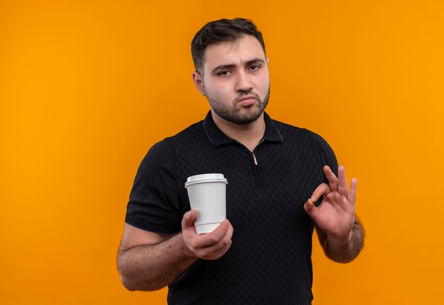 Jeune homme barbu en chemise noire tenant une tasse de café faisant signe ok à la confiance