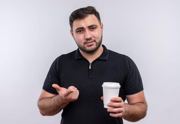Jeune homme barbu en chemise noire tenant une tasse de café regardant la caméra mécontent des gestes avec la main