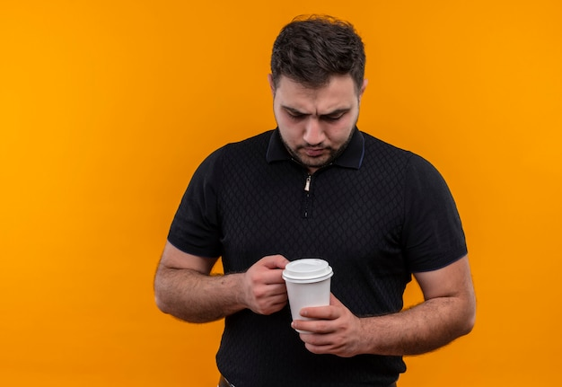 Jeune homme barbu en chemise noire tenant une tasse de café regardant la caméra avec le visage fronçant les sourcils