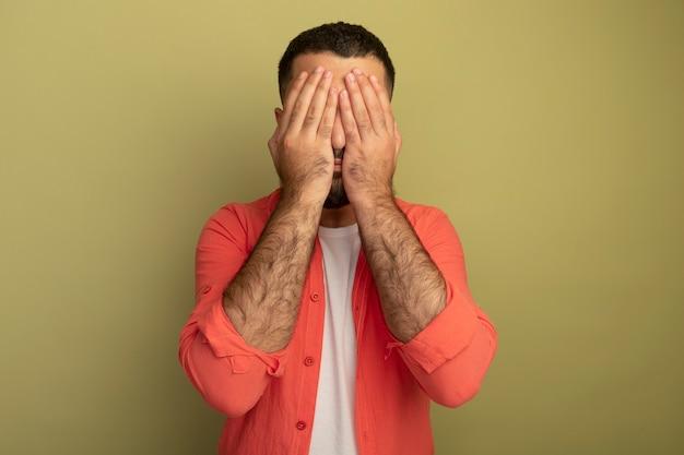 Jeune homme barbu en chemise orange couvrant les yeux avec les mains debout sur un mur léger