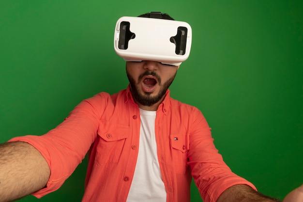 Jeune homme barbu en chemise orange avec des lunettes de réalité virtuelle faisant des gestes avec les mains debout sur le mur vert