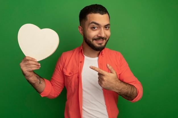 Jeune homme barbu en chemise orange tenant un coeur en carton à la recherche de pointage avec l'index en souriant debout sur le mur vert