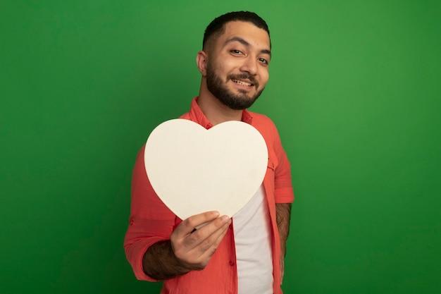 Jeune homme barbu en chemise orange tenant coeur en carton à la recherche avec le sourire sur le visage debout sur le mur vert