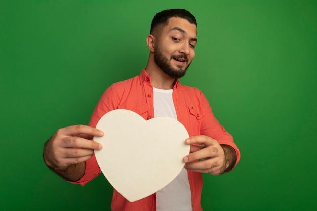 Jeune homme barbu en chemise orange tenant coeur en carton en le regardant avec le sourire sur le visage debout sur le mur vert