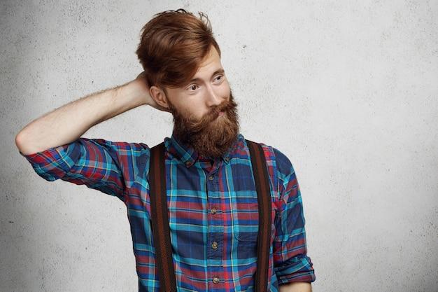 Jeune homme barbu confus douteux portant chemise à carreaux et bretelles se grattant la tête dans l'incertitude, détournant les yeux avec une expression interrogative et interrogative sur son visage, pensant à quelque chose