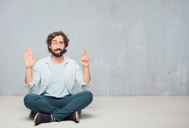 Jeune homme barbu cool assis sur le sol. fond de mur de grunge