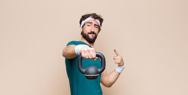 Jeune homme barbu cool au gymnase avec un haltère. concept sportif