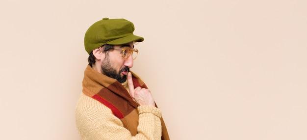 Jeune homme barbu cool demandant le silence et le calme, faisant des gestes avec le doigt devant la bouche, disant chut ou gardant un secret