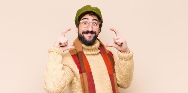 Jeune homme barbu cool encadrant ou décrivant son propre sourire avec les deux mains, à la recherche de concept de bien-être positif et heureux