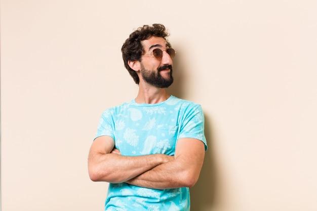 Jeune homme barbu cool regardant sur le côté avec les bras croisés et lunettes de soleil