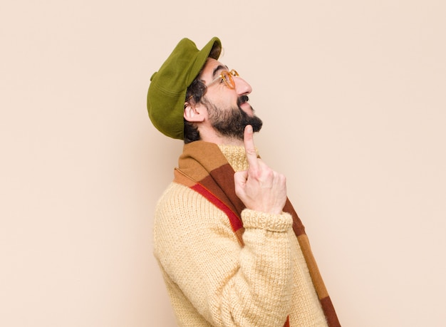 Jeune homme barbu cool souriant joyeusement et joyeusement, pointant vers le haut d'une main pour copier l'espace