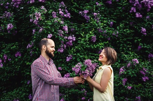 Jeune homme barbu dans la nature donne à une fille un bouquet de fleurs lilas.