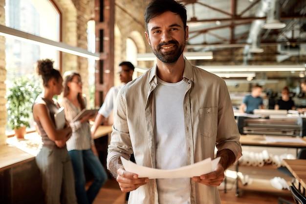 Jeune homme barbu dans des vêtements décontractés tenant des documents et regardant la caméra avec le sourire au bureau