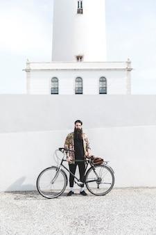Jeune homme barbu debout devant le phare