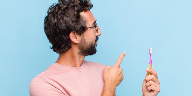 Jeune homme barbu debout et pointant vers l'objet sur l'espace de copie, vue arrière