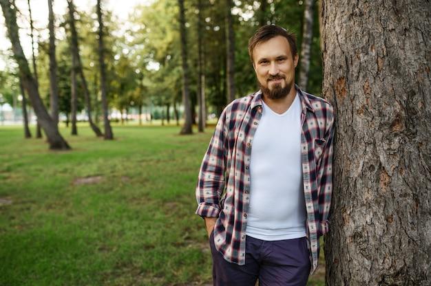 Jeune homme barbu debout près de l'arbre dans le parc d'été