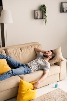 Jeune homme barbu en dépression en raison de l'isolement du coronavirus allongé sur un canapé et couvrant le visage avec la main