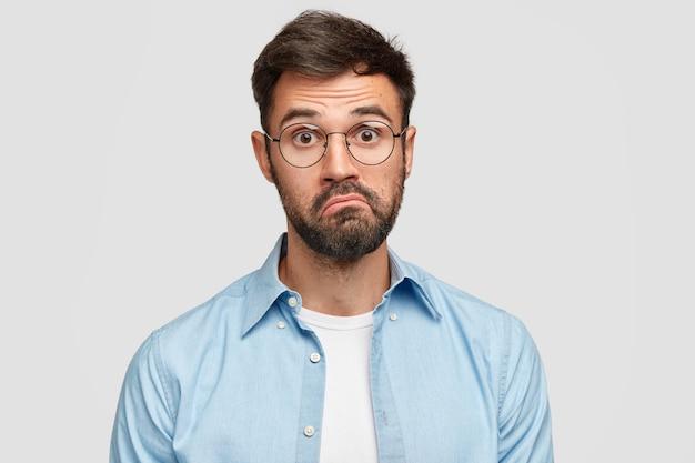 Un jeune homme barbu douteux serre les lèvres avec étonnement, a une expression perplexe