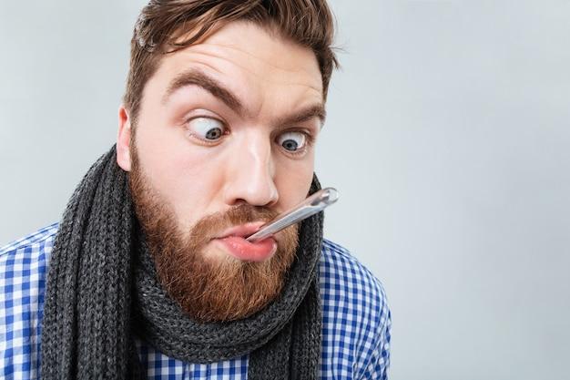 Jeune homme barbu drôle en écharpe avec thermomètre dans sa bouche sur mur blanc