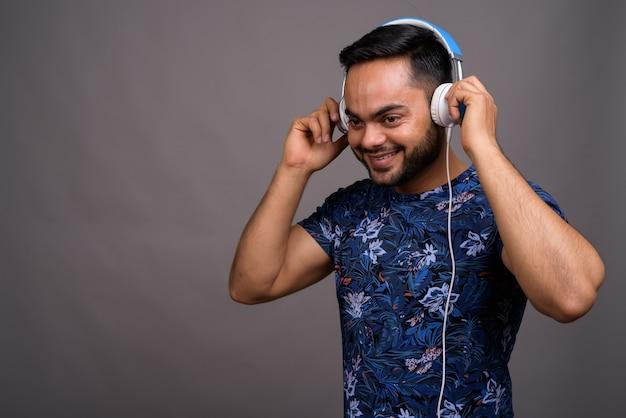 Jeune homme barbu écoutant de la musique contre le gris