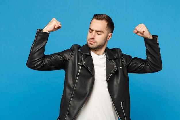 Jeune homme barbu élégant en t-shirt blanc avec veste en cuir noir montrant des biceps, muscles isolés sur fond de mur bleu portrait en studio. concept de mode de vie des émotions sincères des gens. maquette de l'espace de copie.