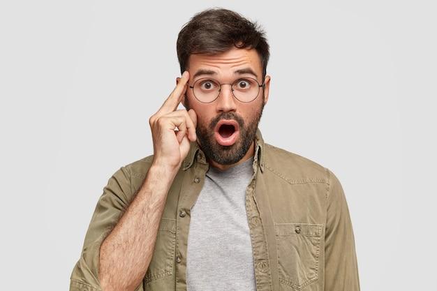 Un jeune homme barbu émotif garde la mâchoire baissée, le doigt sur la tempe, voit quelque chose d'étonnant et de choquant
